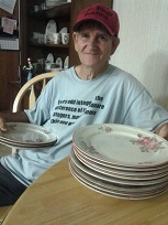 Man holding 3 plates in one hand and 8 plates resting on the table